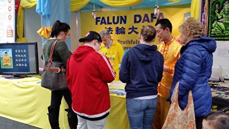 参加健康展的游人在法轮功摊位前驻足聆听真相。(李凌云/大纪元)