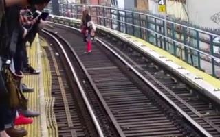 一名穿著紅色長褲和花紋外套的女性乘客,在J列車軌道中間行走。 (Gabbie提供)