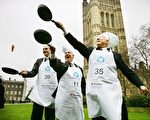 London, UNITED KINGDOM: Participants in the '2007 Parliamentary Pancake Race' undertake a practice session on College Green in aid of charity early Shrove Tuesday morning in central London, 20 February 2007. From left to right, Members of Parliament Daniel Kawczynski (L), Lindsay Hoyle (C) and Brian Iddon (R) took part in the race. The MP's won the race against a team from the House of Lords and the media. The race is in aid of charity and supports Rehab UK, a brain injury charity. AFP PHOTO/ADRIAN DENNIS 2007年,议员们在议会大厦前的维多利亚塔花园(Victoria Tower Garden)前投掷平锅中的煎饼的历史照片。( ADRIAN DENNIS/AFP/Getty Images)