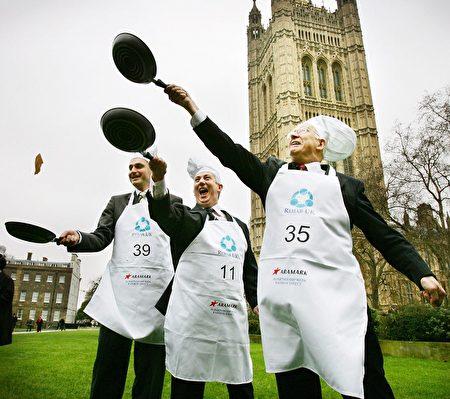 2007年,议员们在议会大厦前的维多利亚塔花园(Victoria Tower Garden)前投掷平锅中的煎饼。( ADRIAN DENNIS/AFP/Getty Images)