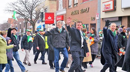 波士顿圣派翠克节大游行开始,麻州州长查理•贝克(中,著黑衣牛仔裤者)、波士顿市长马丁•华殊(右二,著黑色西服者)、麻州联邦众议员斯蒂芬•林奇(右一,著黑风衣者)等政要走在游行的前列,向观众挥手致意。(贝拉/大纪元)