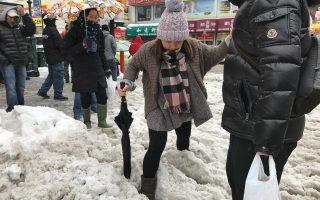 法拉盛7號線地鐵口積雪未清,給行人過馬路帶來不便。 (林丹/大紀元)