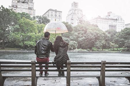 下雨天,夫婦坐一條長凳在中央公園,