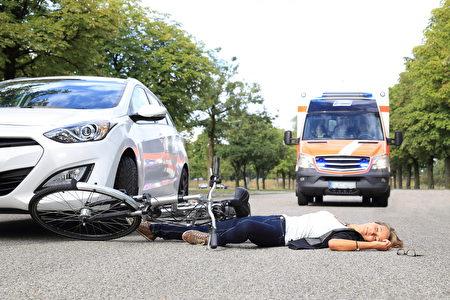 Frau liegt nach Fahrradunfall auf Strae mit Krankenwagen