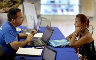 民众正在跟健保公司员工咨询投保事宜。 (Joe Raedle/Getty Images)