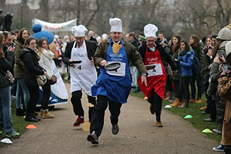 LONDON, ENGLAND - FEBRUARY 12: The annual Parliamentary Pancake Race takes place in front of the Houses of Parliament on Shrove Tuesday on February 12, 2013 in London, England. Now in it's 16th year, the annual Pancake Race, which raises money for the charity Rehab, sees teams of politicians and journalists racing in a circuit whilst tossing pancakes in frying pans. The team of MPs won this year's event. (Photo by Dan Kitwood/Getty Images)