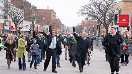波士顿圣派翠克节大游行开始,波士顿市长马丁•华殊(著黑色西服者)、麻州联邦众议员斯蒂芬•林奇(著黑风衣者)、麻州州长查理•贝克(后,著黑衣牛仔裤者)等政要走在游行的前列,向观众挥手致意。(贝拉/大纪元)