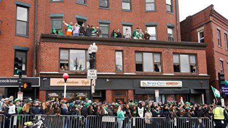 穿戴着翡翠绿服饰、佩带着三叶苜蓿的当地居民和游客,观看波士顿圣派翠克节游行。(贝拉/大纪元)