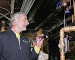 马里兰州能源专家Jim Singer正在检查供热管道。(新唐人电视台)