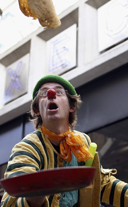 LONDON, ENGLAND - FEBRUARY 28: A contestant dressed as a clown takes part in the annual pancake race in Spitalfields Market, February 28, 2006 in London, England. Participants are expected to don costumes and race a short sprint tossing a pancake as they go to celebrate Shrove Tuesday. (Photo by Marta Travesset/Getty Images)