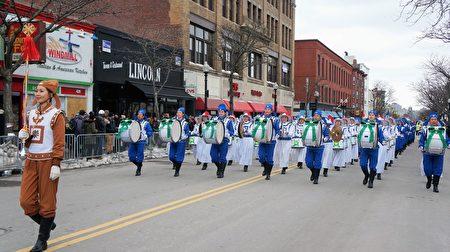 """波士顿圣派翠克节游行队伍中,身着蓝白相间中国传统服装的160名乐团成员,手举""""法轮大法""""横幅,方阵整齐,气势雄壮。(贝拉/大纪元)"""
