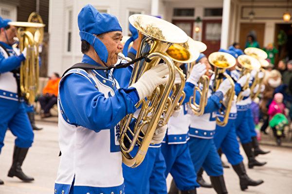 """由法轮功学员组成的天国乐团游行队伍格外引人注目。身着蓝白相间中国传统服装的160名乐团成员,手举""""法轮大法""""横幅,方阵整齐,鼓号悠扬,气势雄壮,震撼人心。(戴兵/大纪元)"""