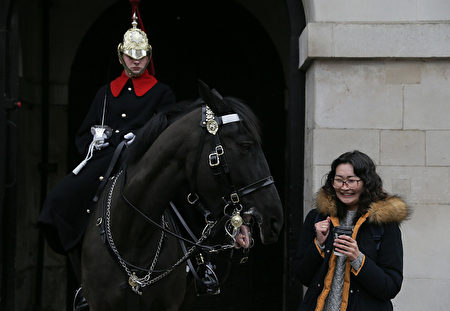 TOPSHOT - A tourist gestures as she poses next to a member of the Household Cavalry Mounted Regiment on Whitehall in central London on February 25, 2017. / AFP / Daniel LEAL-OLIVAS (Photo credit should read DANIEL LEAL-OLIVAS/AFP/Getty Images)