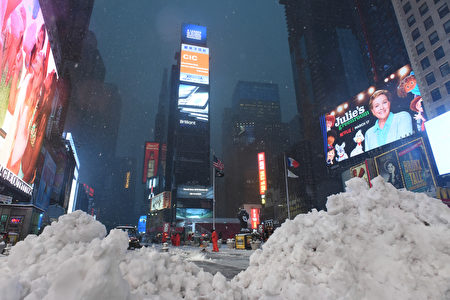 Piles of snow are seen as workers clear the sidewalks in Times Square during a snowstorm in New York on March 14, 2017. Winter Storm Stella dumped snow and sleet Tuesday across the northeastern United States where thousands of flights were canceled and schools closed, but appeared less severe than initially forecast. After daybreak the National Weather Service (NWS) revised down its predicted snow accumulation for the city of New York, saying that the storm had moved across the coast. / AFP PHOTO / Eric BARADAT (Photo credit should read ERIC BARADAT/AFP/Getty Images)