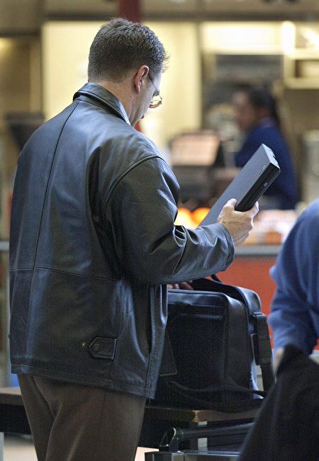一名旅客在机场安检后将笔电放入手提行李。(Tim Boyle/Getty Images)
