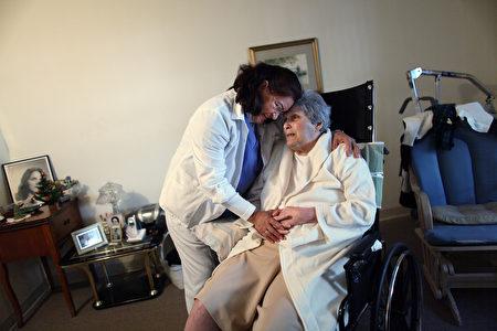 迈阿密Hhome保健护士在访问老年病患时拥抱她。(Joe Raedle/Getty Images)