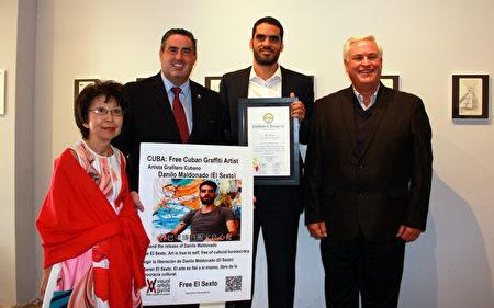 """古巴艺术家""""良心犯""""达尼洛·马尔多纳多(右二)在驻留画廊展出作品,唐尼市议员Alex Saab(左二)、前市议员Mario Guerra(右一)与维权人士刘雅雅(左一)前来参与。(徐绣惠/大纪元)"""