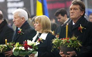 """2006年11月25 日,乌克兰总统尤先科(右)主持""""1932—1933年大饥荒档案揭密展""""。民众点燃蜡烛悼念在斯大林暴政下的死难者。(GENIA SAVILOV/AFP/Getty Images)"""