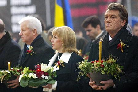 2006年11月25 日,烏克蘭總統尤先科(右)主持「1932—1933年大饑荒檔案揭密展」。民眾點燃蠟燭悼念在斯大林暴政下的死難者。(GENIA SAVILOV/AFP/Getty Images)