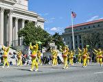 在众多的游行团体中,由粉色莲花和金色流苏装饰的法轮大法花车,以及身着亮黄色衣服的法轮大法腰鼓队,在游行的队伍中显得格外显眼。(李莎/大纪元)