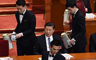 2016年3月9日,中共「兩會」上男服務生在給習近平和中共政治委員倒水。(GREG BAKER/AFP/Getty Images)