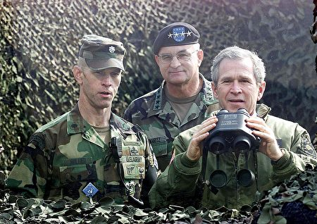 US President George W. Bush (R) looks across the demilitarized zone into North Korea through a bullet proof glass from Outpost Ouellette, a US Military base in the demilitarized zone between South and North Korea, 20 February 2002. At left is Lt. Col. William Miller, commander joint security area, and at center is General Thomas Schwartz, commander in charge of the US forces in Korea. Bush accused North Korean leader Kim Jong-Il, during a joint press conference with his South Korean counterpart Kim Dae-Jung, of abusing his people but said the US would not invade the North. Bush is here for a three-day official visit as part of his three Asian nations tour. AFP PHOTO by Luke FRAZZA / AFP PHOTO / LUKE FRAZZA