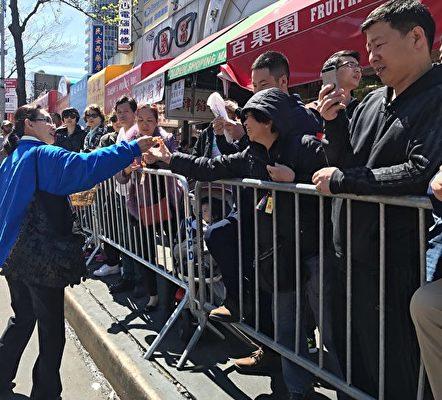 2017年4月23日,紐約部份法輪功學員在法拉盛舉行盛大遊行,路邊的民眾從法輪功學員手上接過蓮花。(林丹/大紀元)