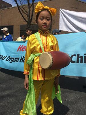 2017年4月23日,纽约部分法轮功学员在法拉盛举行纪念四二五和平上访18周年大游行。图为腰鼓队中的小弟子。(施萍/大纪元)
