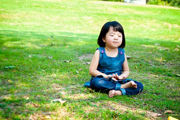 小亚裔女孩实践的在室外公园正念凝思。(fotolia)