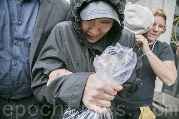 4月6日下午2时左右,李凡妮在律师们的簇拥下快速闪避记者,上车离去。(曹景哲/大纪元)