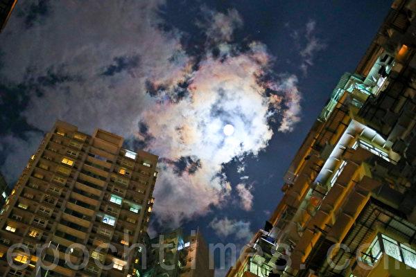 香港稠密高楼群的特殊景观,曾是好莱坞电影变形金钢、攻壳机动队等影片的取景场地之一。图为2017年4月8日晚,香港鲗鱼涌高楼群在明月相伴下,彩云片片的美景。(余钢/大纪元)