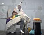 法藝術家普安什瓦爾在美術館中坐著孵蛋,遭批:剝奪小雞擁有母親的權利。 (STEPHANE DE SAKUTIN/AFP)