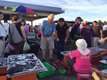 《台灣澎湖群島》特輯,入圍第44屆艾美獎4項大獎,圖為清晨在馬公第三漁港根兜售魚貨的小販聊天(許瓊文攝影)。(觀光局提供)