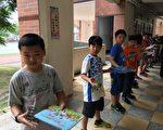 五谷国小图书馆,学生心手相连传书。(苗县府/提供)