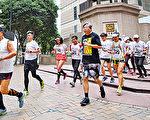 今年是六四事件28周年,香港支联会昨日举行毋忘六四长跑,由石硖尾的六四临时纪念馆,跑到中联办。图为参与人士经过铜锣湾时代广场。(蔡雯文/大纪元)