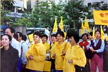 1999年12月,王大姐(图左二,穿黄色练功服)在香港法会前,参加游行。(王友凤女士提供)