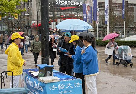 2017年4月22日,部分温哥华法轮功学员在温哥华艺术馆前集会纪念四.二五,行人纷纷驻足聆听真相,观看横幅展板,或签名支持制止中共迫害。(大宇/大纪元)