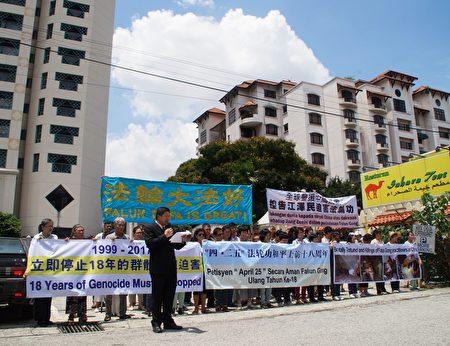 """纪念""""四•二五""""和平上访十八周年,部分马来西亚法轮功学员顶着烈日,在中共驻马大使馆附近举行集会,法轮功学员代表王先生宣读马来文文告。(杨晓慧/大纪元)"""