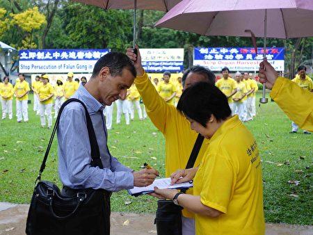"""2017年4月18日,新加坡部分法轮功学员,冒着小雨在芳林公园举行集体炼功、征签等活动,纪念""""四•二五""""万名法轮功学员和平上访十八周年。(Tony/大纪元)"""