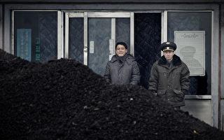 習近平向川普表達,在朝鮮問題上願意和美國保持交流及協調。北京近日在具體行動方面,似也展現「要管好朝鮮」的意向。圖為兩名朝鮮人站在煤炭前。(WANG ZHAO/AFP/Getty Images)