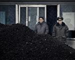 金正恩政權最大的收入來源,是每年向中共銷售數百萬噸媒炭,根據其官方統計,2015年和中共的煤炭交易金額占其出口值的三分之一。圖為兩名朝鮮人站在煤炭前。(WANG ZHAO/AFP/Getty Images)