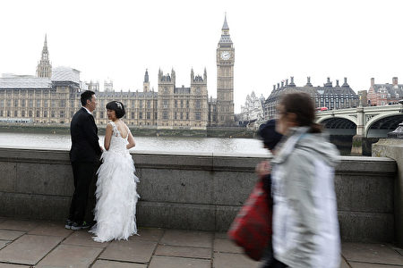 A couple prepare to pose for their wedding pictures by Westminster Bridge in central London on March 23, 2017 after the bridge reopened to traffic following its closure during the March 22 terror attack.  Britain's parliament reopened on Thursday with a minute's silence in a gesture of defiance a day after an attacker sowed terror in the heart of Westminster, killing three people before being shot dead. Sombre-looking lawmakers in a packed House of Commons chamber bowed their heads and police officers also marked the silence standing outside the headquarters of London's Metropolitan Police nearby.  / AFP PHOTO / Adrian DENNIS        (Photo credit should read ADRIAN DENNIS/AFP/Getty Images)