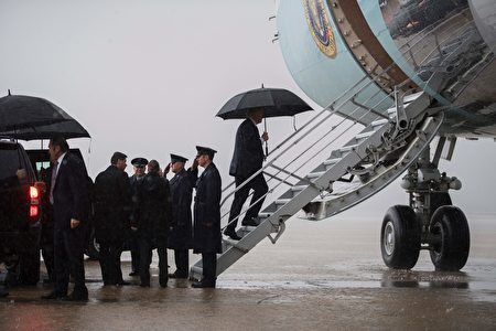 在馬里蘭州安德魯斯空軍基地,川普在雨中登上「空軍一號」飛往佛州。 (Photo credit should read JIM WATSON/AFP/Getty Images)