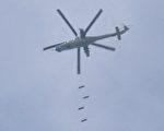 4月8日,一架敘利亞軍直升機在南部一座被反對派控制的城市,投放炸彈。 (MOHAMAD ABAZEED/AFP/Getty Images)
