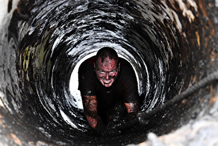 PORTADOWN, NORTHERN IRELAND - APRIL 09: A race goer makes his way up a manhole as competitors take part in the annual McVities Mud Madness 8km cross country run on April 9, 2017 in Portadown, Northern Ireland. The two lap race over twenty five obstacles is in aid of the Marie Curie charity. (Photo by Charles McQuillan/Getty Images)