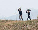 在金氏共产专制政权下,数十年来朝鲜人民过着与世隔绝的生活。图为2名朝鲜妇女要到河边洗衣。(JOHANNES EISELE/AFP/Getty Images)