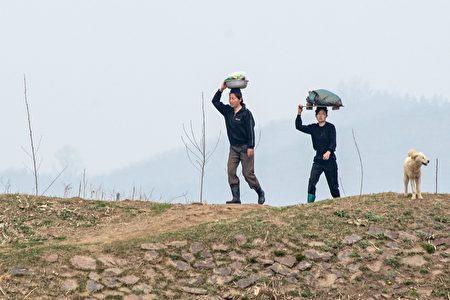 在金氏共產專制政權下,數十年來朝鮮人民過著與世隔絕的生活。圖為2名朝鮮婦女要到河邊洗衣。(JOHANNES EISELE/AFP/Getty Images)