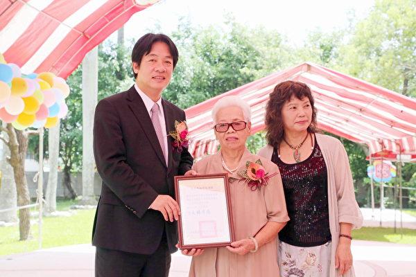 魏朱莲招(中)捐资重建崇和国小校园,台南市长赖清德颁发感谢状表扬。(台南市政府提供)