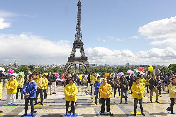 图为法国法轮大法弟子在巴黎铁塔前举行活动的场面。(大纪元)