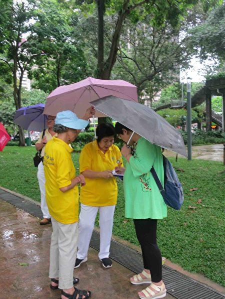 """2017年4月18日,新加坡部分法轮功学员,冒着小雨在芳林公园举行集体炼功、征签等活动,纪念""""四•二五""""万名法轮功学员和平上访十八周年。(王秀/大纪元)"""